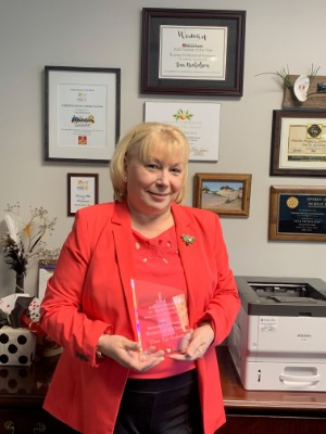 Tina Nicholson holding 2020 Business Professional Woman of the Year Award