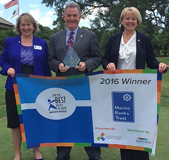 Photo of Marine Employees holding 2016 Best Places to Work Indian River Banner