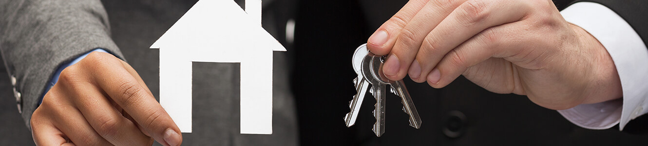 Photo of a man holding a cardboard cut out of a house and a set of keys, meant to represent purchasing a new home.