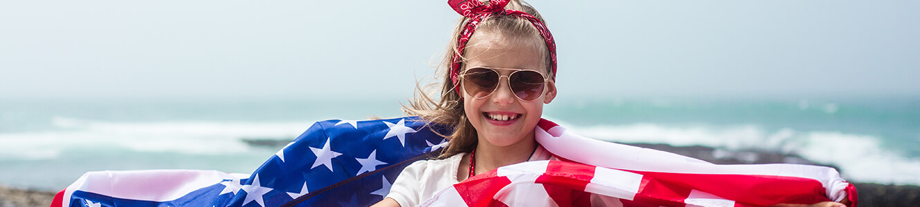 An image of a young girl wrapped in an american flag
