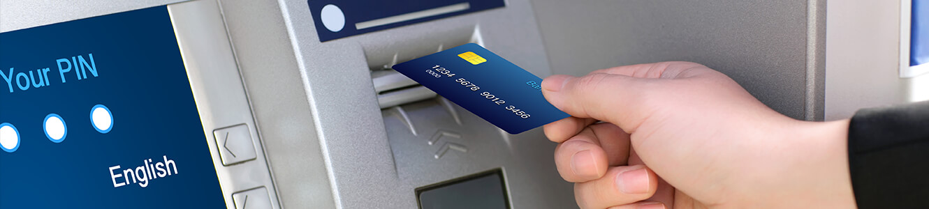 Photo of someone putting their ATM card into an ATM machine