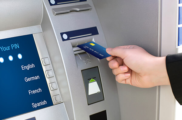 Image of someone putting their debit card into the ATM machine.